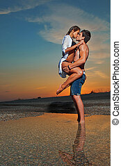 Couple on the beach at sunset - young couple kissing at the...