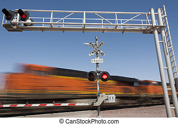 train speeding by railroad crossing in the countryside