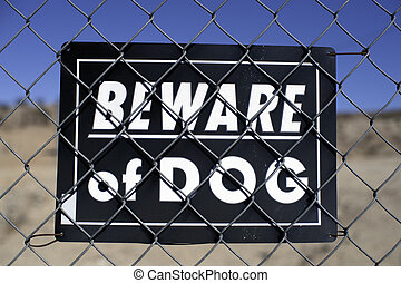 beware of dog sign on a wire fence