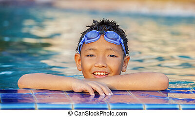 little boy playing in swimming pool