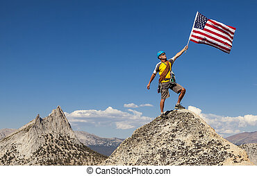 Mission Accomplished - Rock climber raises the flag on the...