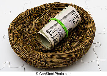 Nest Egg - Roll of fifty dollars bills sitting in nest on a...