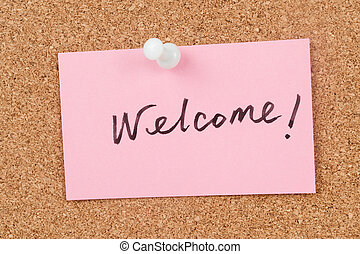 Welcome word written on paper and pinned on corkboard