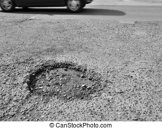 Pothole in road - Motorcar drives past a pothole in road