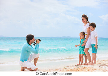 Family beach vacation - Young man making photo of his wife...