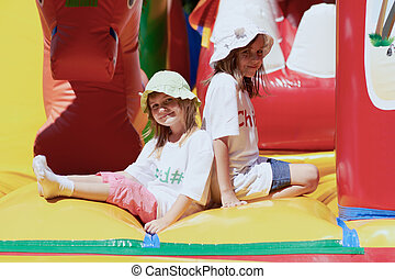 Cute little sisters in a jumping castle - Pretty young girls...