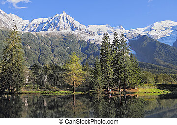 Reflections of snow-capped peaks and coastal trees in city...