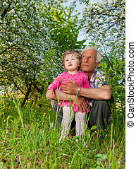 grandfather with his granddaughter on a small nature