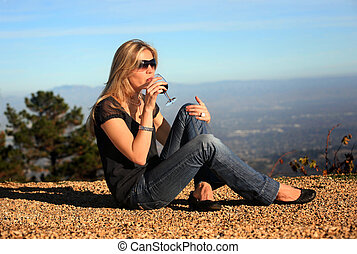Wine tasting - A young blond woman tasting wine outdoors
