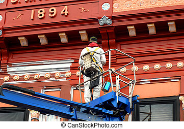 Applying New Paint - Painter applies new paint to historic...