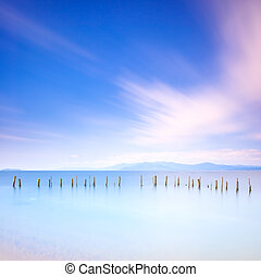 Poles and soft water on sea landscape. Long exposure. -...