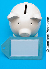 Savings Interest Rate - Piggy bank with blank tag on blue...