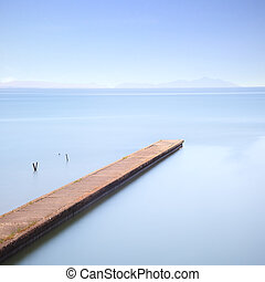 Concrete pier or jetty on a blue sea Hills on background...