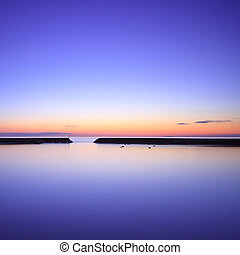 Concrete pier silhouette and blue ocean on twilight sunset -...