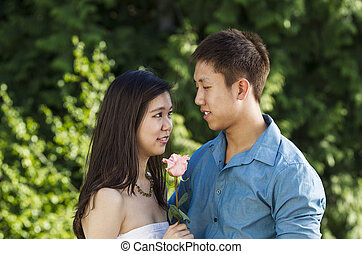 Young couple in love with pink rose in between them