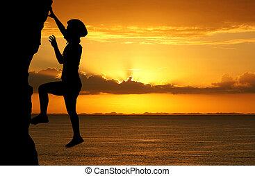 Mountain Climber - Girl climbing a tall mountain at sunset