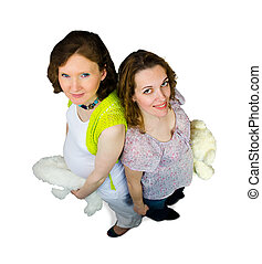 Two pregnant women play with teddy toys