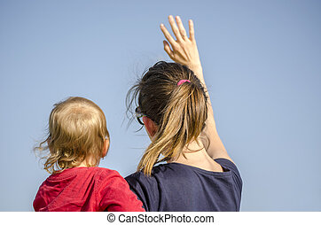 Mum and son waving. View from behind.