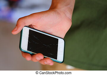 Broken Phone - A close up view of someone holding a broken...