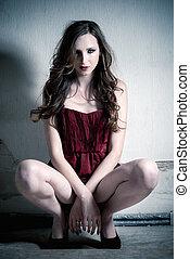 Fashion portrait of beautiful brunette woman in red dress