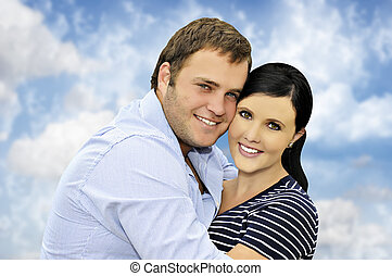 Beautiful happy  young couple with cloud background
