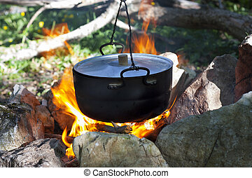 pot on the fire, tourists kettle on hot campfire. Camping...