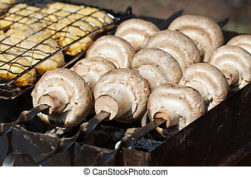 Cooking mushrooms champignons Agaricus bisporus on grill