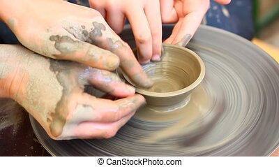 Work of artist - A potters hands guiding a child hands to...