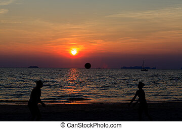 Asian couple play volleyball on the beach and sunset