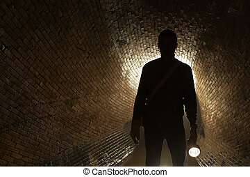 Mystery man - Silhouette man in underground old sewage...