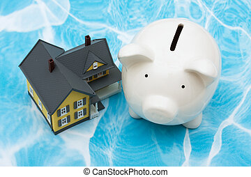 Home Finances - Model house with piggy bank on blue...