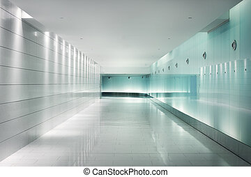 Back-lighted white glass walls in an underground metro station corridor. Contemporary interior design. This is part of the Square-Victorial tunels in Montreal