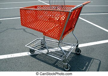 Grocery Cart - A bright orange grocery cart alone in a...