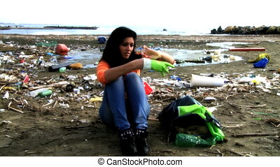 Sad woman in dirty beach - Sad social worker unable to clean...