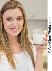 Woman drinking glass of milk in kitchen