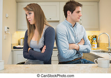 Divided couple with arms crossed in kitchen