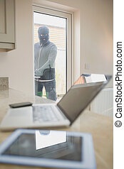 Burglar opening kitchen door and looking at laptop on...