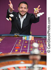 Man throwing chips onto roulette ta