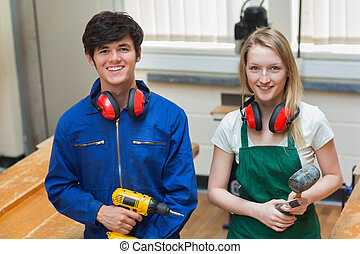 Two students holding a driller and - Two students standing...