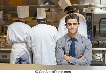 Waiter standing in the kitchen - Waiter standing in a busy...