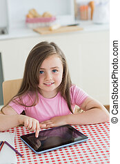 Happy little girl using tablet computer at kitchen table