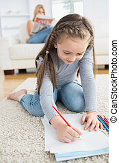 Little girl drawing sitting on floor