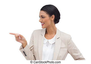 Profile view of a smiling businesswoman pointing on a white...
