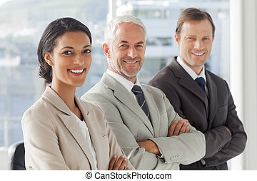 Three business people standing with their arms crossed in...