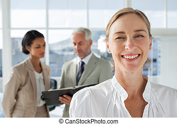 Cheerful businesswoman standing with colleagues working behind