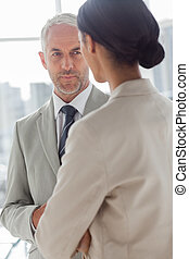 Concentrated businessman listening to colleague in the...