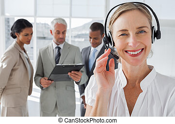 Close up of smiling woman standing with a headset with...