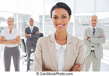 Attractive businesswoman with arms crossed standing in front...