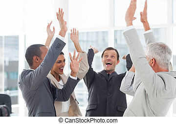 Group of smiling business people raising their hands in the...