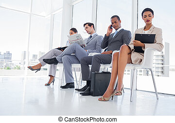 Business people working while waiting in an office